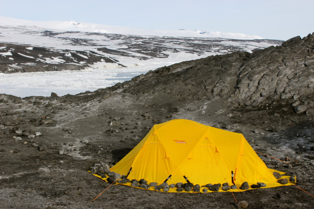 Setting up camp with backdoor bay behind frozen over with sea ice.